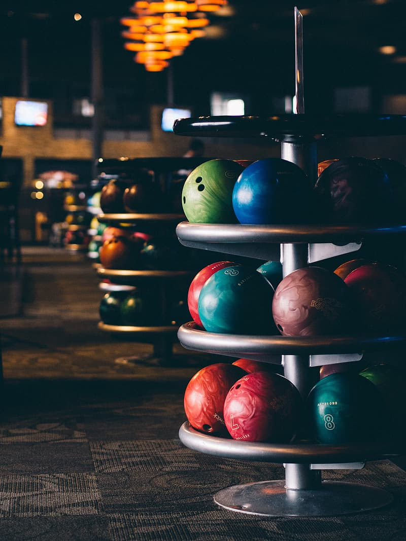 Selective focus of assorted-color bowling balls on rack