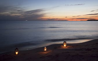 Three beige lamps on brown sand