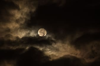 Full moon surrounded by dark clouds