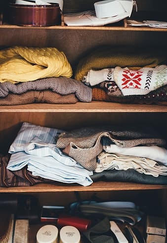 Assorted clothes filled wooden rack