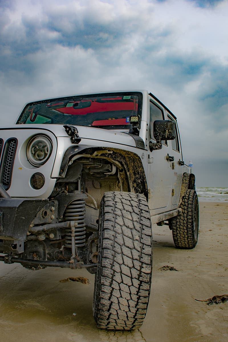 White and red jeep wrangler on beach during daytime