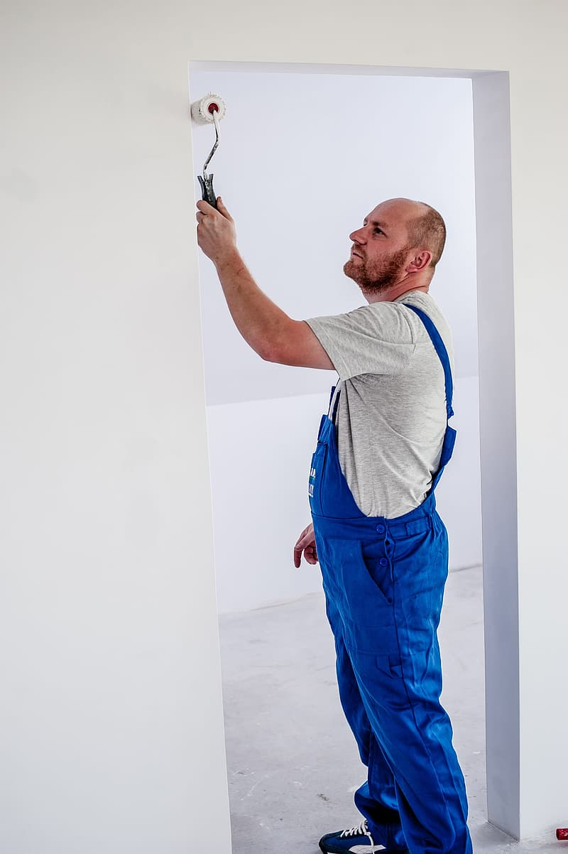 Man standing while painting the doorway using white paint roll