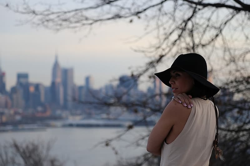 Woman in white tank top and black fedora hat standing near body of water during daytime