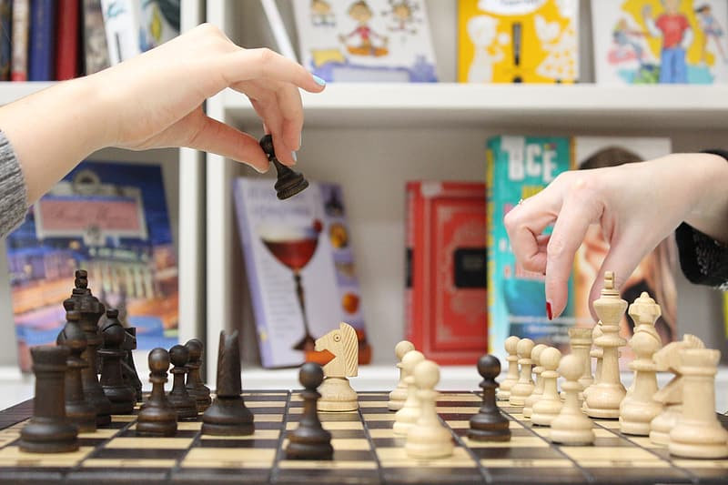 Two people playing chess in library