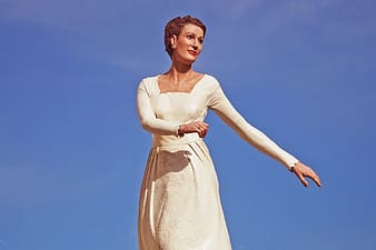 Woman in white sleeveless dress standing under blue sky during daytime