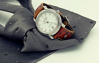 Round silver-colored bezel analog watch on top of gray necktie