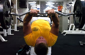 Man in yellow crew-neck t-shirt lifting a barbel