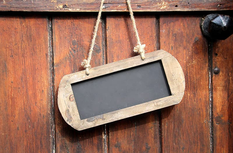 Brown wooden sign board hanging on wall