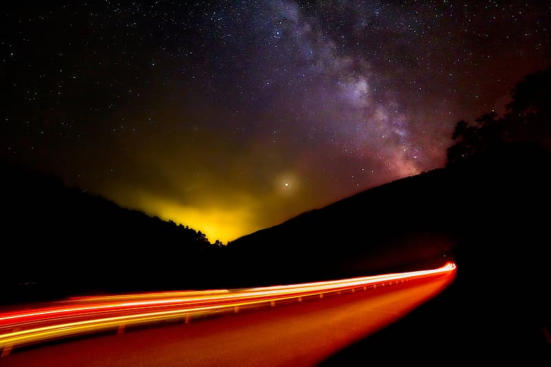 Time lapse photography of stars over the road during night time