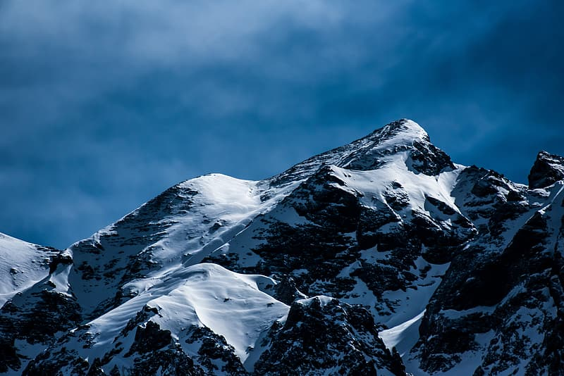 Snow covered mountain under white sky