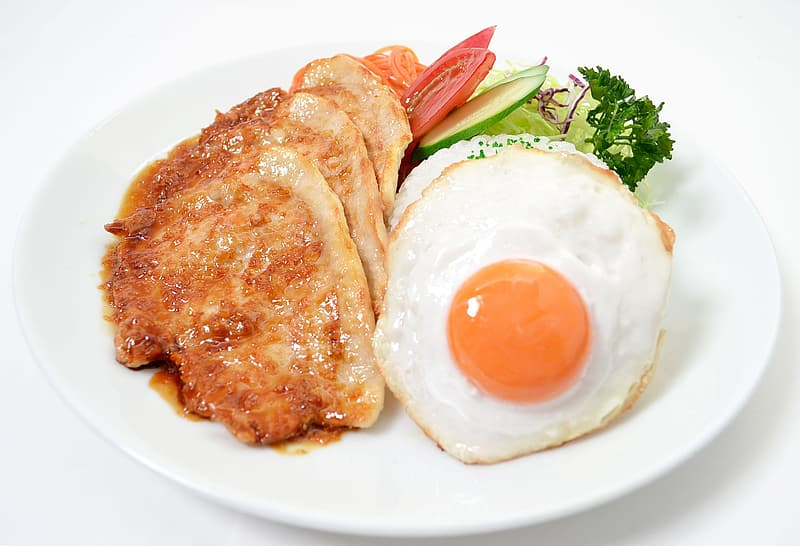 Fried pork cutlet with fried egg on plate