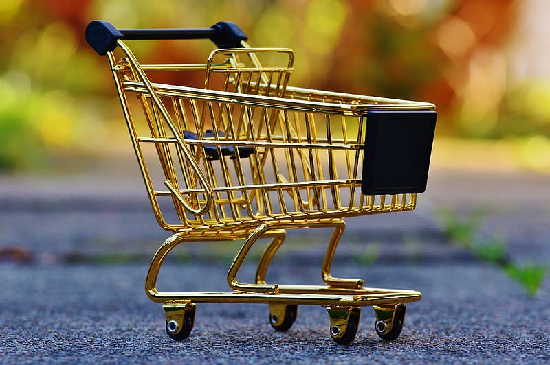 Selective photo of copper and blue shopping cart on gray concrete pavement