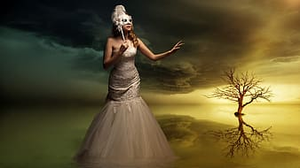 Woman in white trumpet dress standing away from bale tree