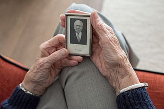 Person holding white and black digital device