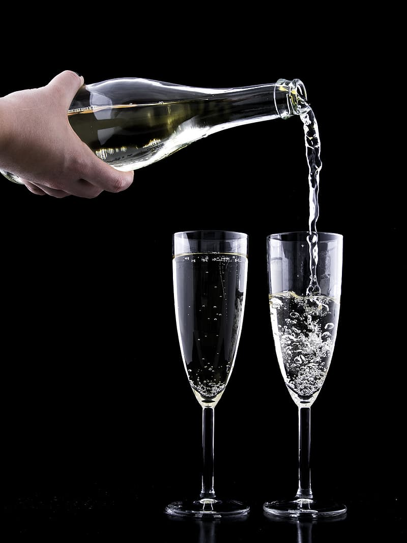 Person pouring champagne on two glasses