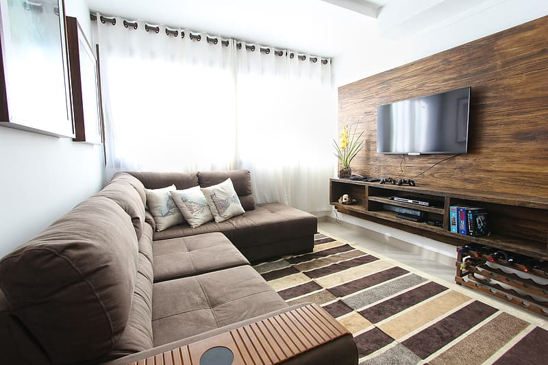 Tufted brown sectional couch near modern brown wooden TV unit