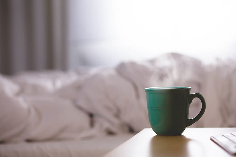 Green teacup near white bed sheet