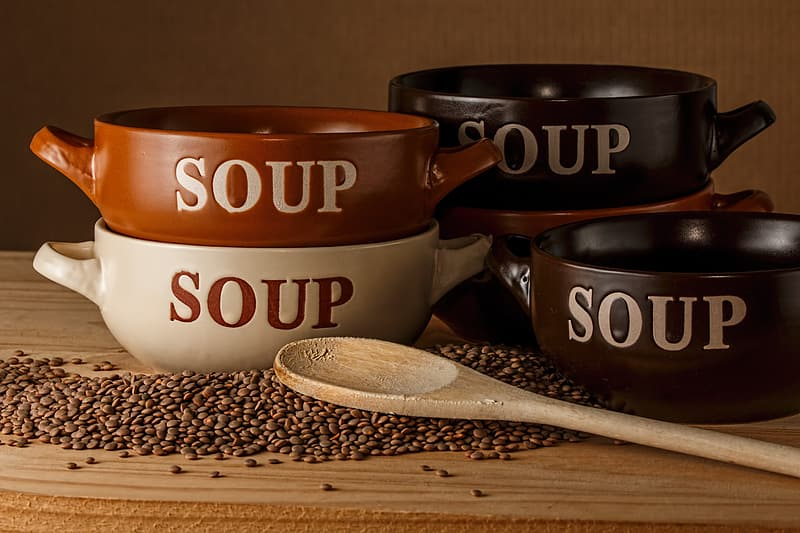 Assorted color Soup bowls with brown wooden spoon on beige wooden table