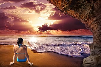 Woman in blue bikini standing on beach shore during sunset