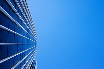 Low-angle photo of curtain wall high-rise building under blue clear sky at daytime