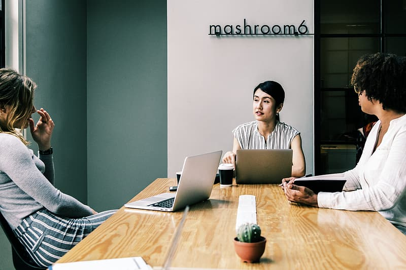 Woman in white and black stripe shirt using macbook pro