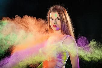 Woman wearing white tank tops with orange and multicolored smoke