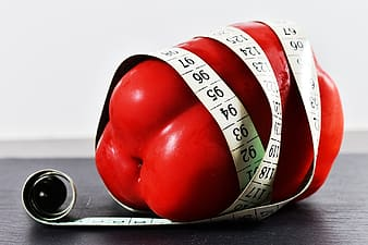 Red bell pepper covered with tape measure