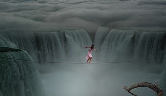 Photograph of woman about to cross on rope above waterfalls