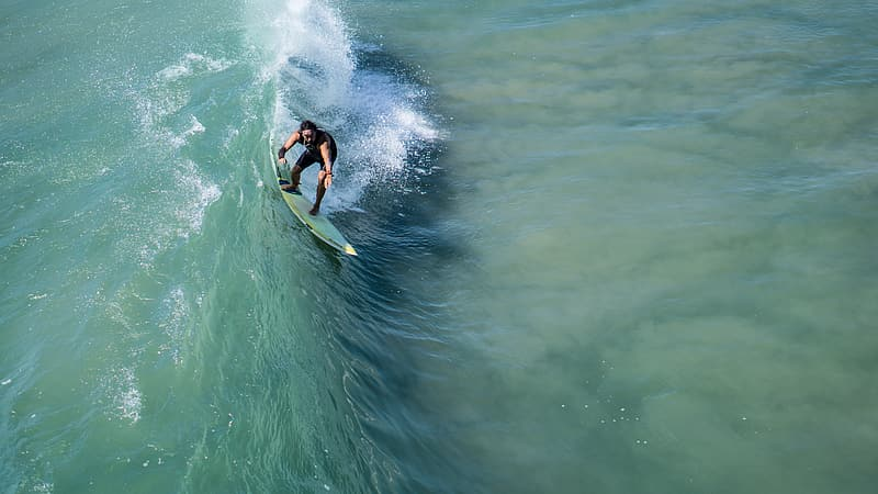 Aerial photography of man surfing ocean wave during daytime