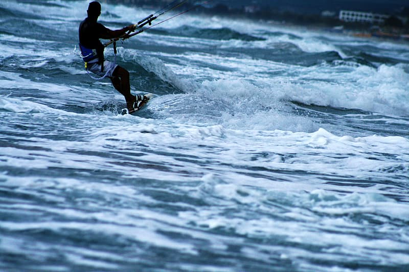 Man in blue shirt and black shorts surfing on sea waves during daytime