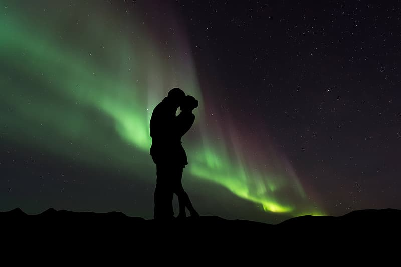Two man and woman kissing on mountain