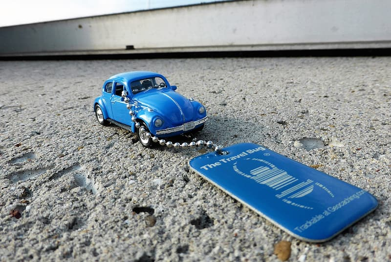 Close up photo of blue Volkswagen Beetle coupe keychain on gray surface