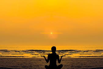 Silhouette of woman meditating near body of water during sunset