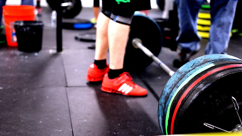 Person standing in front of barbell