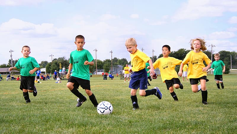 3 boys playing soccer on green grass field during daytime
