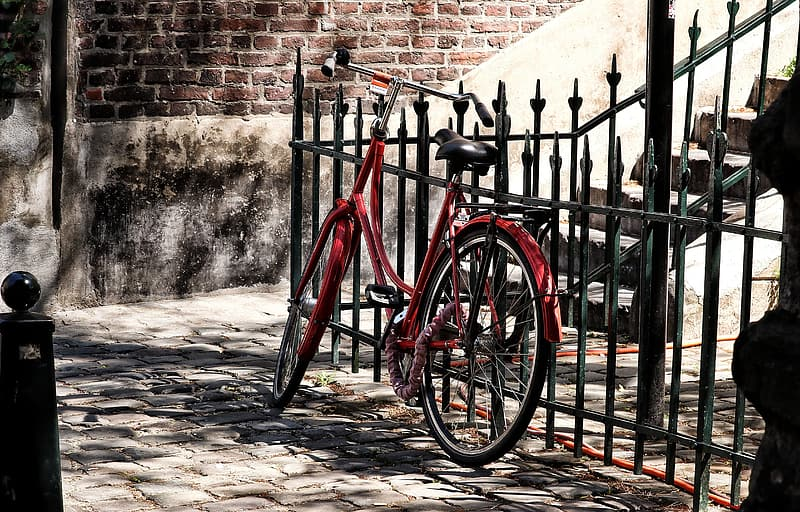 Red commuter bike parked beside brown concrete wall during daytime