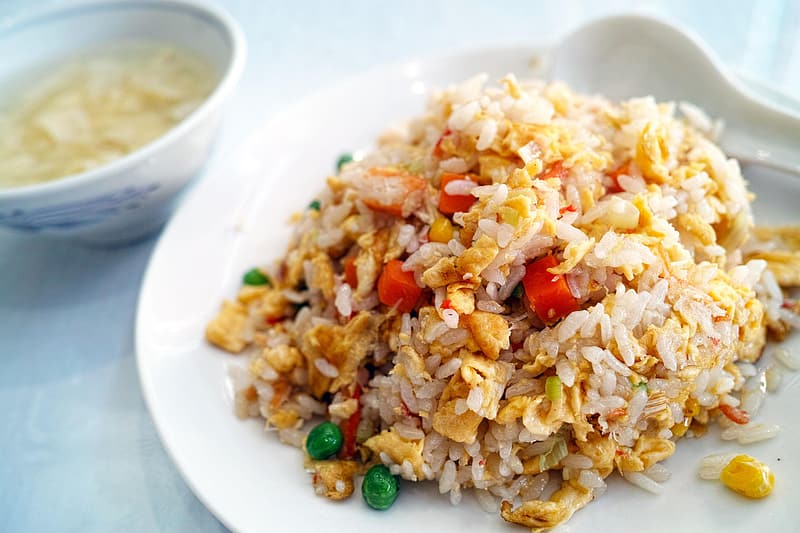 Fried rice with mixed vegetables on white ceramic plate