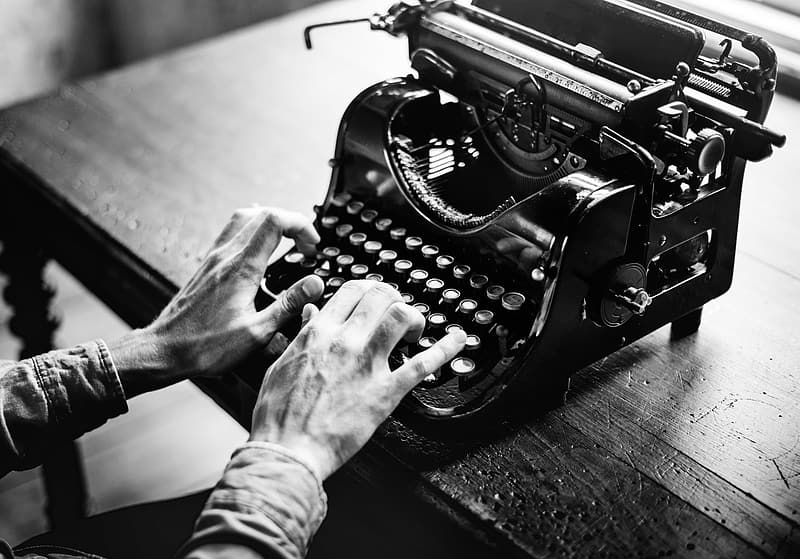 Grayscale photo of person using typewriter