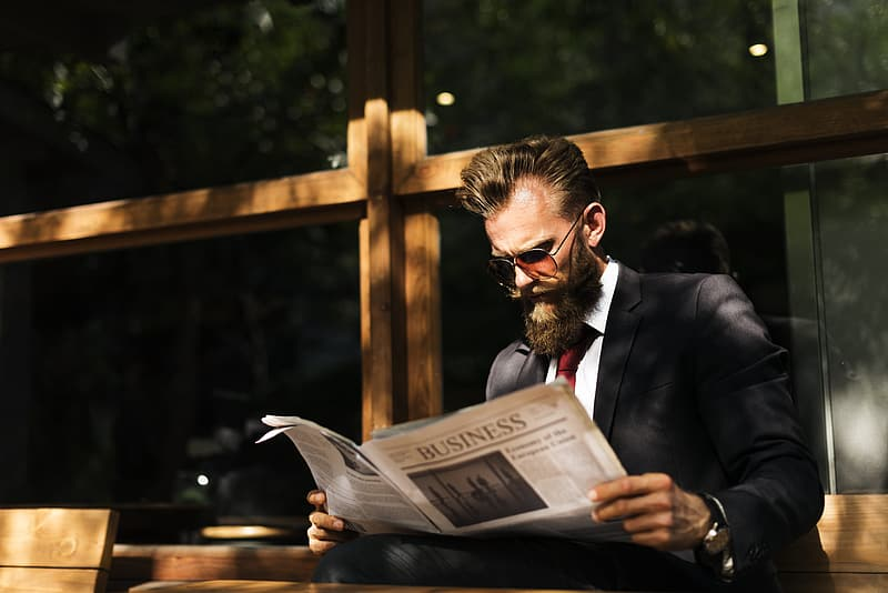 Man wearing black and white tuxedo suit reading newspaper during daytime