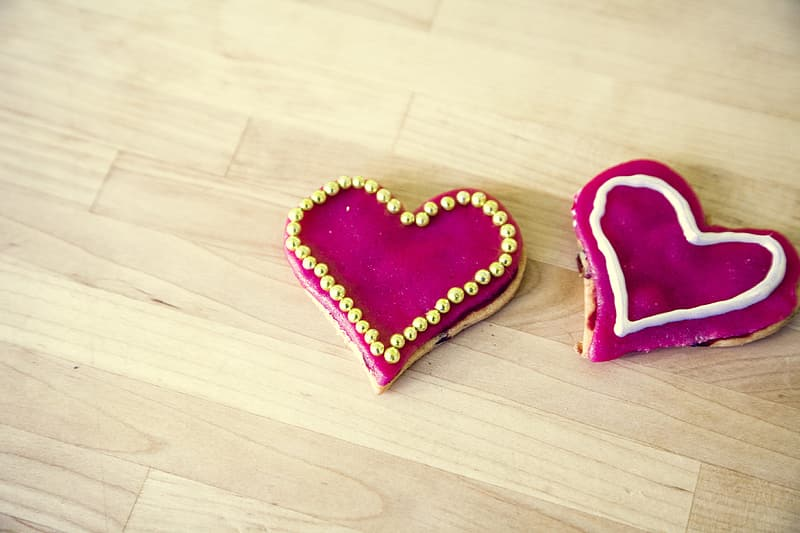Heart shaped cookies with pink cream and beads on top