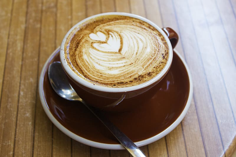 Cappuccino cup on red saucer with teaspoon
