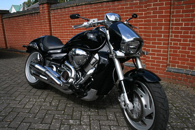 Black cruiser motorcycle on gray concrete pavement