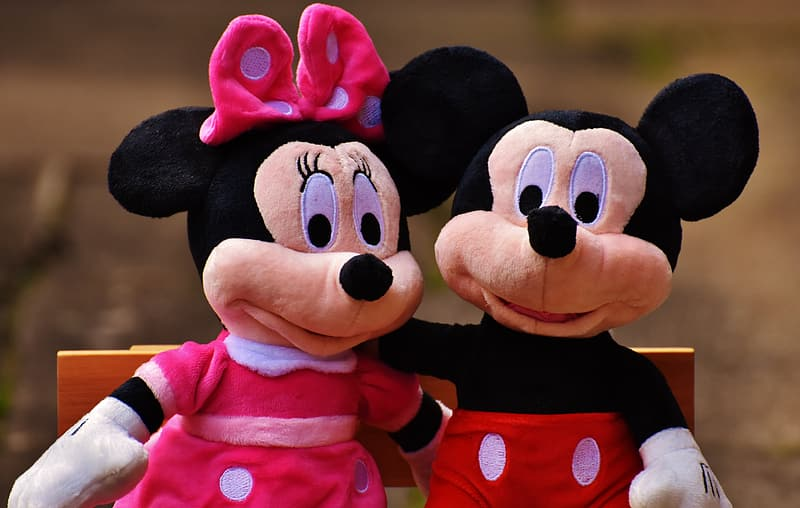 Mickey Mouse and Minnie Mouse plush toys sitting on brown wooden bench