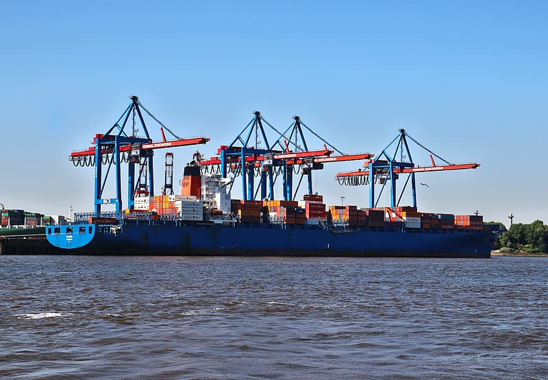 Crane inside the cargo ship on body of water during daytime