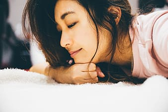 Woman in pink shirt laying on white textile