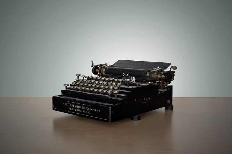 Black typewriter on brown surface wallpaper