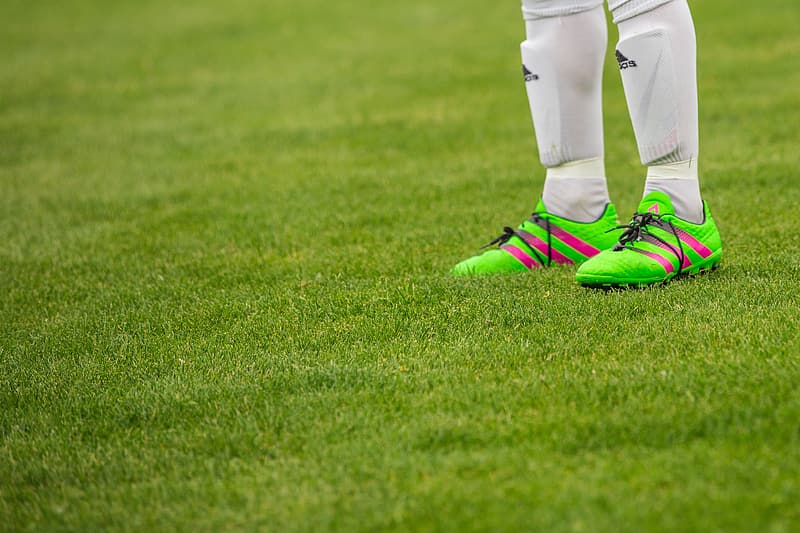 Selective focus photography of green cleats