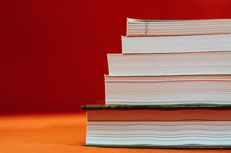 Pile of five books on brown surface