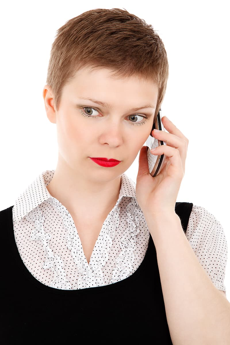 Woman with white and black collared shirt using white QWERTY phone