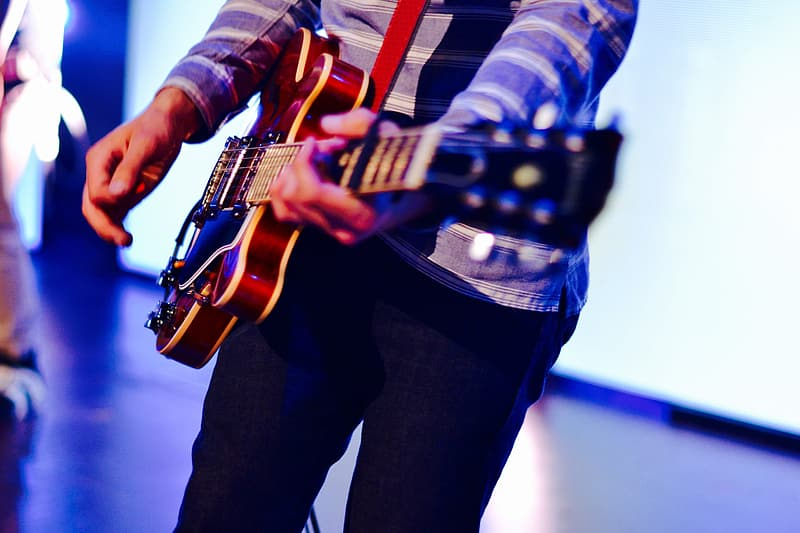 Man playing guitar on stage at a music concert